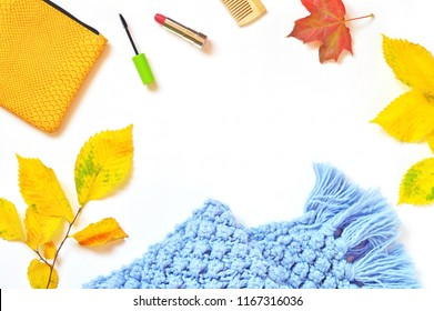Autumn feminine background. Women's stuff and yellow leaves. Cosmetic bag, mascara, red lipstick and blue woolen scarf. Cozy mockup with makeup cosmetics for beauty blog