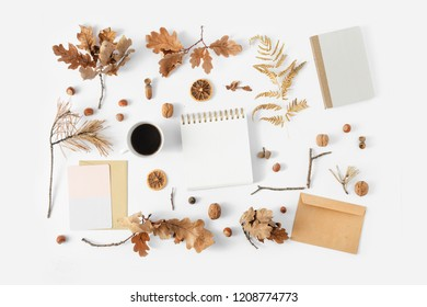 Autumn feminine workspace, desk with notepad, envelope, cup coffee, card and dry autumn leaves on white background, top view. Stylish office
