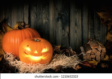 Autumn festive still life with evil smiling pumpkin on straw and leaves on background of wooden wall for Halloween and place for your text