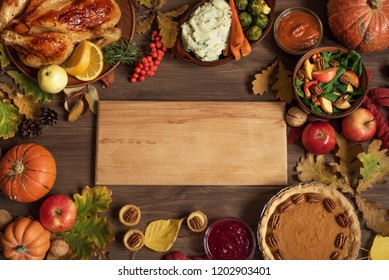 Autumn festive Thanksgiving dinner background with Turkey and traditional sides dishes around Wooden Board, copy space for text, menu design, seasonal food concept.