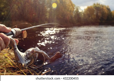 Autumn fishing spinning in his hand