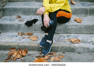 Autumn fitness workout and healthy sporty lifestyle concept. Close up of female athlete in sportswear holding bottle of water and sitting in stairs with leaves around.