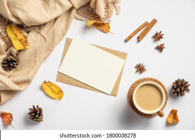 Autumn flat lay composition. Craft paper envelope, blank card mockup, coffee cup, cinnamon sticks, beige scarf, pine cones on white background. Autumn hygge style desk table or winter holiday concept.