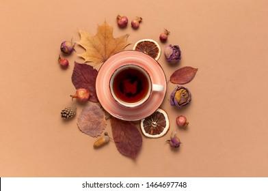 Herbstflachlage. Teebeutel, trockene, helle Blätter im Herbst, Rosenblumen, orangefarbener Kreis, Zapfen, dekoratives Granatapfelat, Zimtstangen auf braunem beigem Hintergrund, Draufsicht. Herbst, Herbst-Konzept