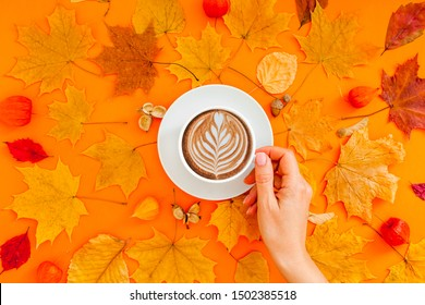 Autumn flat lay composition with dry leaves wreath frame and coffee latte cup in woman hand on bold orange color background. Creative autumn thanksgiving, fall, halloween concept. Top view, copy space