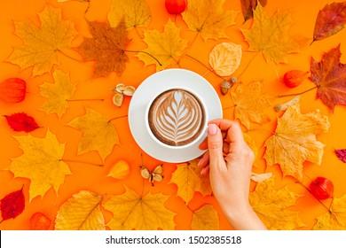 Herbstflache Laienzusammensetzung mit trockenen Blättern Kranzrahmen und Kaffeetasse in Frau Hand auf fett orangefarbenem Hintergrund. Kreatives Herbstdanken, Herbst, Heiligtum. Draufsicht, Kopienraum