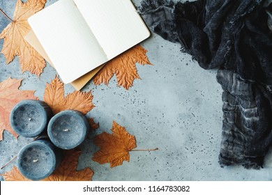 Autumn flat lay composition on a grey concrete background. Maple leaves, the open notebook with empty sheets, black aromatic candles and warm scarf. Mockup, top view.