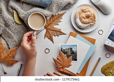 Autumn flat lay concept. Woman's home office desk with coffee and autumn leaves. Top view
