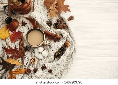 Autumn flat lay, cozy inspirational image.Hygge lifestyle. Coffee cup with  fall leaves, anise,herbs, acorns, nuts , cinnamon, cotton on white knitted sweater. Autumn mood.