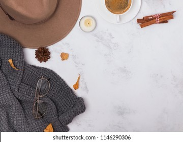 Autumn flat lay with hat, coffee, dry leaves and spices on the marble background