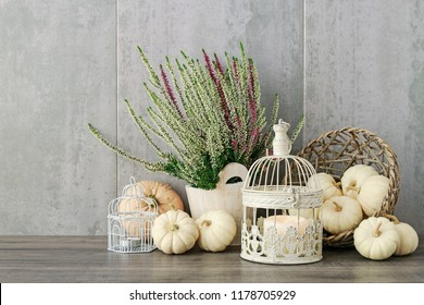 Autumn floral arrangement with white and violet heather (calluna vulgaris), baby boo pumpkins and candles inside the vintage bird cages.