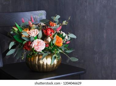 Autumn floral bouquet in colored punpkin vase on black chair, copy space