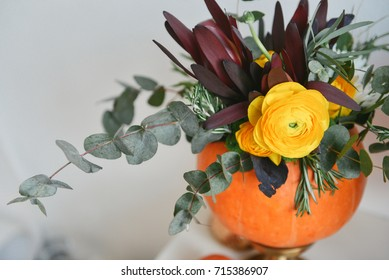 autumn floral bouquet in a pumpkin vase for Halloween. Table setting for wedding