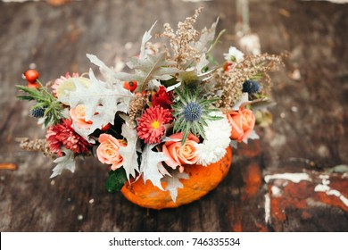 Autumn floral bouquet in a pumpkin vase for Halloween.