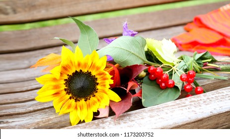 Autumn flowers arrangements made of sunflowers, leaves and berries on rustic vintage background.