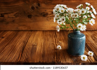 Autumn flowers in a ceramic vase on old rustic wooden table