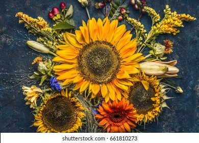 Autumn flowers and leaves composition with sunflowers on dark rustic background , top view, fall nature
