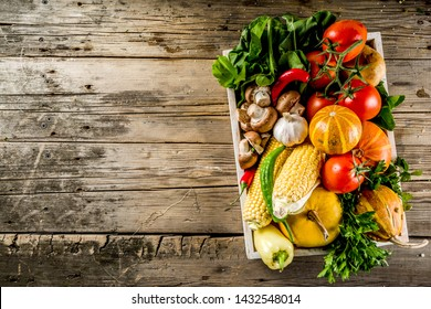 Autumn food concept. Healthy organic harvest vegetables and ingredients pumpkin, greens, tomatoes, corn, wooden kitchen table background. Thanksgiving seasonal cooking ingredients.