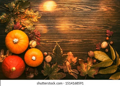 Autumn food top view, Thanksgiving or Halloween background: pumpkins, nuts, fallen leaves and spices on brown wooden background. Seasonal fall background for Thanksgiving dinner