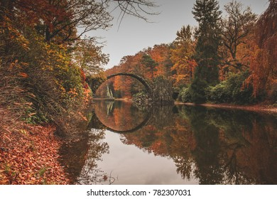 Autumn in the forest with fairytale bridge over the lake