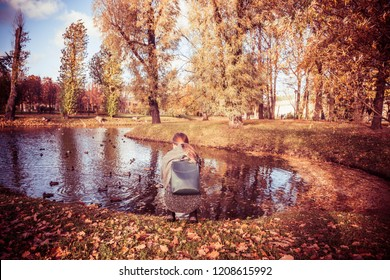 autumn forest landscape, a girl with a backpack feeds ducks at the lake