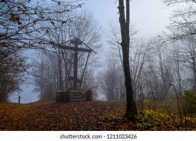 Autumn forest mist cross view. Scary forest mist cross in autumn fog. Mysterious forest mist in autumn fog scene. Giant cross in autumn forest mist landscape