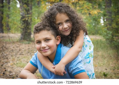 In the autumn forest, a small curly sister lovingly embraces her older brother lovingly.