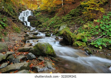 Autumn forest waterfall and rocks with yellow leaves