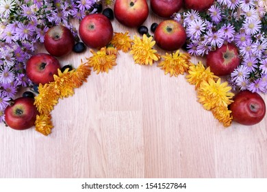 Autumn frame from fruits of apples and grapes and different colors. Autumn yellow flowers and violet oak decorate an unusual frame on a wooden background.