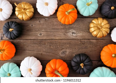 Autumn frame of various colorful pumpkins on a rustic wood background. Top view with copy space.