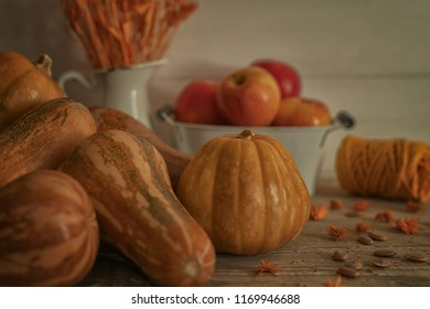 Autumn fruit and vegetables background. Fall Thanksgiving seasonal. Nature background. Wooden old table in an autumnal warm day and flowers in rustic vase. Selective focus. Toned image.