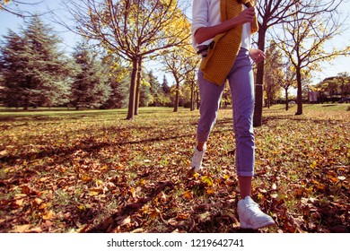 autumn fun young woman running on brown leaves in between trees in a garden or forest low section crop