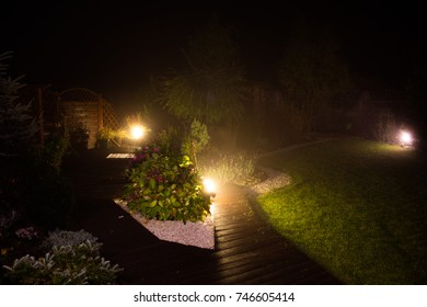 autumn garden lit in the evening lit by lamps