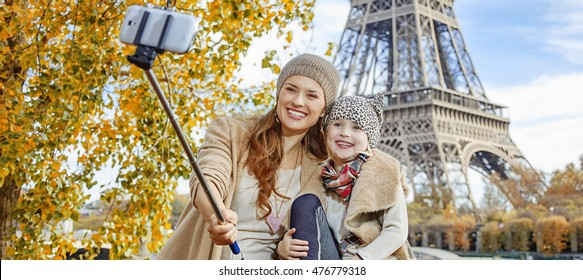 Autumn getaways in Paris with family. happy mother and child tourists on embankment near Eiffel tower in Paris, France taking selfie using selfie stick