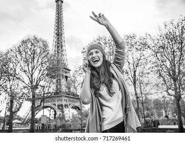 Autumn getaways in Paris. happy young woman in Paris, France using a mobile phone and handwaving
