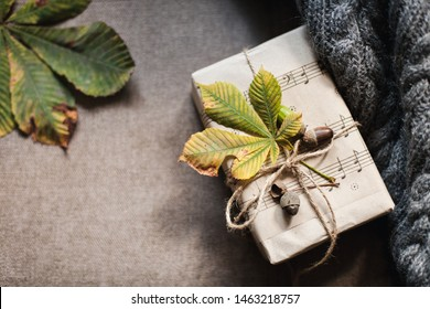 Autumn gifts with fallen leaves. Present for Thanksgiving day is wrapped in kraft paper in rustic style with natural materials. Cozy still life in sunlight. Flat lay, copy space.