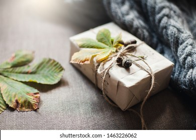 Autumn gifts with fallen leaves. Present for Thanksgiving day is wrapped in kraft paper in rustic style with natural materials. Cozy still life in sunlight.