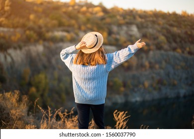 Autumn girl in blue sweater and hat standing backwards and admire nature lake view. Autumn forest colors with girl back view. Autumn portrait.
