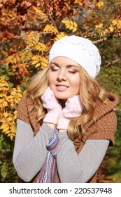 Autumn girl in city park in the warm scarf, glowes and hat