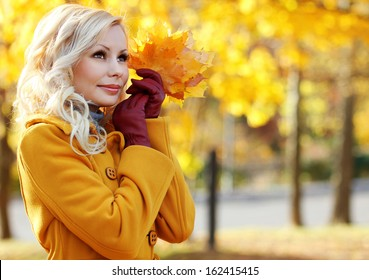 Autumn Girl. Fashion Blonde Beautiful Woman with Maple leaves in hand. Fall park