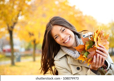 Autumn girl playing in city park. Fall woman portrait of happy lovely and beautiful mixed race Asian Caucasian young woman in forest in fall colors.