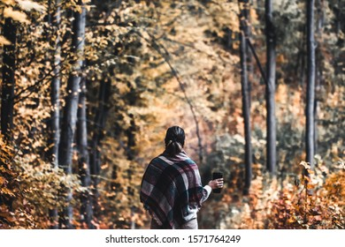 Autumn girl standing backwards and watching nature. Autumn forest colors with girl back view. Outdoor autumn landscape. Orange autumn portrait. Orange tranquility - woman watching woods outdoor