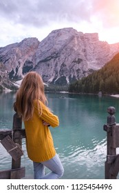 autumn - girl and view of well-known tyrolean lake lago di Braies Dolomites Italy