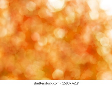 Autumn gold abstract background, blurred sun light - bokeh. Orange, brown and yellow dots.