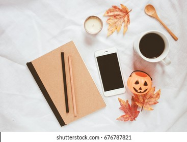 Autumn and halloween style concept, notebook , smartphone, halloween pumpkin, coffee with maple leaves on white bed sheet background