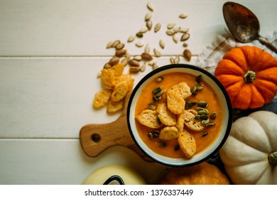 Autumn Halloween or thanksgiving day table setting. Pumpkins, spices, bowl vegetable soup and vintage cutlery on wooden table. Thanksgiving background mock up. Top view, toned image.