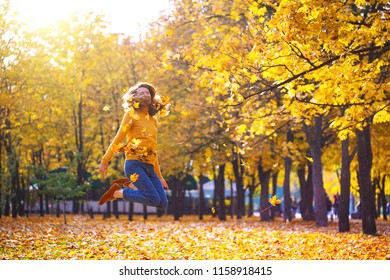 autumn. a happy girl in a park throws yellow leaves