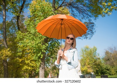 Autumn happy stylish woman with orange umbrella looking up enjoy new day Cute blonde girl stand against fall park and blue sky Empty space for inscription or objects Happy nice season