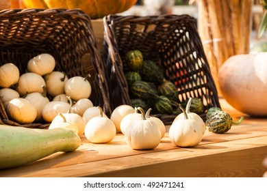 Autumn harvest background with small decorative pumpkins on the table