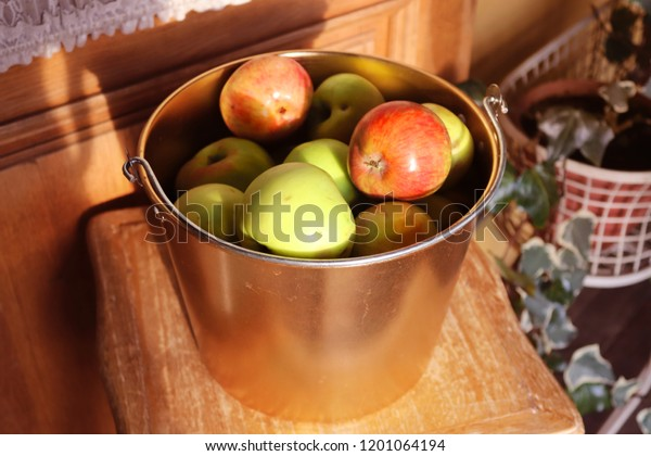 Autumn harvest concept. Fresh apples in a beautiful golden bucket